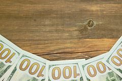 Five One Hudred Dollar Bill On The Rough Wood Background Stock Image