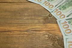 Five One Hudred Dollar Bill On The Rough Wood Background Stock Photography