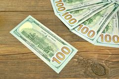 Five One Hudred Dollar Bill On The Rough Wood Background Stock Photo