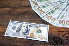 Five One Hudred Dollar Bill On The Rough Wood Background Royalty Free Stock Photo