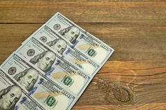 Five One Hudred Dollar Bill On The Rough Wood Background Royalty Free Stock Photos