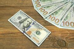 Five One Hudred Dollar Bill On The Rough Wood Background Royalty Free Stock Image