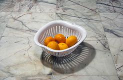 Five orange fruit in a white plastic basket on the Marble floor. Orange is a round juicy citrus fruit with a tough bright reddish-yellow rind stock photos