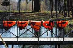 Five orange lifejackets hang on the railing near the pier at the boat station. Gatchina, Russia. Five orange lifejackets hang on the railing near the pier at stock image
