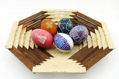 Five painted eggs on a wooden plate Royalty Free Stock Photo