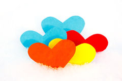 Five paper colored heart shapes in snow Royalty Free Stock Photos