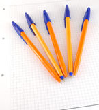 Five pen on the checked paper Stock Photos