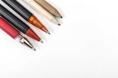 Five pens and pencils in a row on a white background Royalty Free Stock Photography