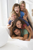 Five people in living room piled up smiling Stock Images