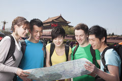 Five people looking at map with Tiananmen Square in background. Royalty Free Stock Images
