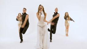 A group of professional actors dancing on a white background. They move synchronously, all movements are very plastic. Five people professional actors dancing on stock footage