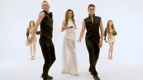 Five people professional actors dancing on white background. Girl-singer in a white dress Two young men in black suits. Are dancing. Two beautiful girls with stock video footage