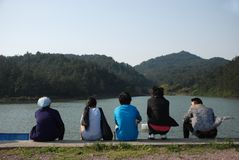 Five people sit near the lake in mountains royalty free stock photo