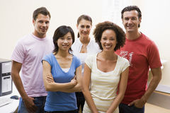 Five people standing in computer room smiling. Looking at camera Royalty Free Stock Images