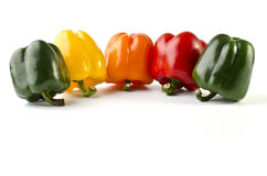 Five peppers arranged in a single line Stock Photos