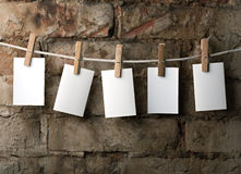 Five photo paper attach to rope with clothes pins. On brick background Royalty Free Stock Image