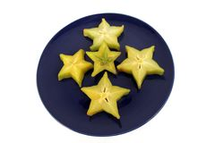 Five pieces of star fruit. Five pieces of starfruit displayed on a blue ceramic plate Stock Photo