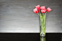 Five pink tulips in a transparent vase on a black table, space for text Royalty Free Stock Photography