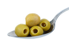 Five pitted green olives in the spoon. Five marinated pitted green olives in the metal spoon isolated on the white background stock photography