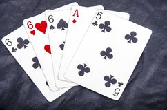 Five playing card`s stud hand three of a kind six and ace a five fun Stock Photos