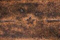 Five-pointed Soviet star on rusty metal. Rusty iron background