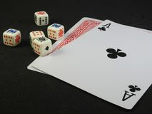 Five poker dices and two playing cards on a black surface. royalty free stock photography