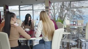 Five positive young Caucasian people sitting at the table in restaurant, talking and laughing. Cheerful friends spending