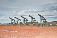 Five pumpjack in a row royalty free stock image