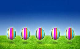 Five Purple striped Easter Egg Hunt on grass stock photo