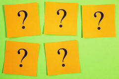Five Question Marks on Orange on Green Background Stock Images