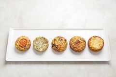 Five quiches on a white plate. Five freshly baked individual mini quiches on a white rectangular plate on a light coloured surface stock image