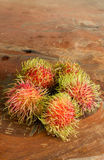 Five rambutans. Rambutans on the wood background Stock Photos