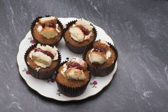 Five raspberry and cream cupcakes on a dark marble background Stock Photo