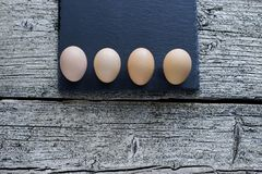 Five raw chicken eggs lie on a black board on a wooden background.  stock photo
