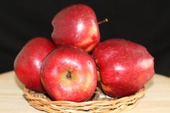 Five red apples on straw plate stock photography