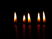 Five red candles burning in the dark - black background Royalty Free Stock Images