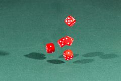 Five red dices falling on a green table. Five red dices falling on a isolated green table stock photography