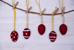 Five Red Easter Eggs Hanging On Line. Five Red And White Easter Eggs Hanging On A Line Which Are Dotted And Striped On White Wooden Vintage Or Rustic Background royalty free stock photo