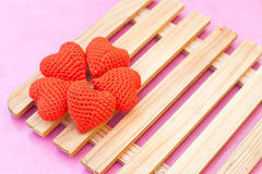 Five red hearts. Put on wood panel on the pink table Stock Photography