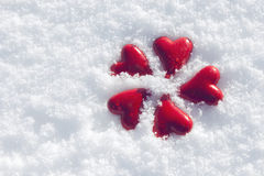 Five red hearts in the snowflakes Stock Images