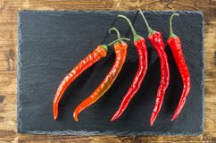 Five red hot peppers diagonally against the background of slate. Five red hot peppers lie on a slate and a wooden surface Stock Photography