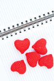 Five red knit hearts. Five hearts knit with red yarn put on the diary Stock Photos