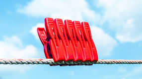 Five red plastic clothespins and the clothesline with blurry blu Stock Photo