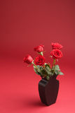 Five red roses in the vase on the red background Royalty Free Stock Images