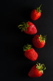 Five red strawberries. On a black background, close-up Stock Image