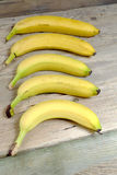 Five ripe bananas on a wooden table Stock Images