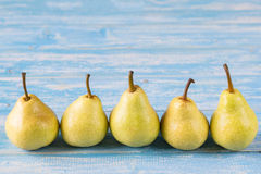 Five ripe pears on a blue wooden table. Ripe pears in a basket on a rustic wooden table. The concept of healthy eating with natural products Royalty Free Stock Image