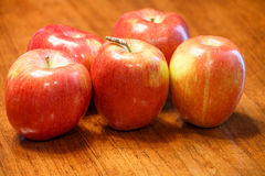 Five Ripe Red Apples on a Wood Table Royalty Free Stock Image