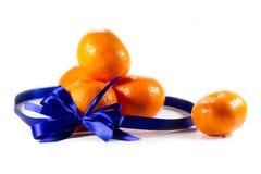 Five ripe sweet mandarins with blue ribbon Royalty Free Stock Photos