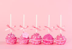 Five romantic pop cake with pink frosting, decorative sprinkles Stock Photo